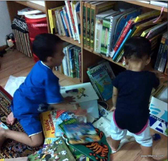Our children busy browsing the mini library at home