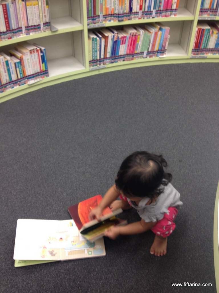 Khadijah busy choosing books in the library